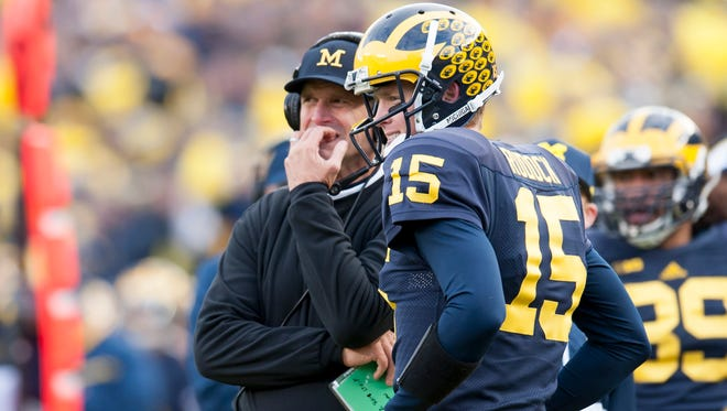 Michigan head coach Jim Harbaugh, left, and quarterback Jake Rudock wait for the results of a touchdown review in the third quarter.