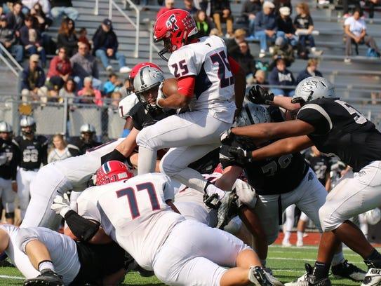 Franklin quarterback Jacob Clark hurdles an offensive