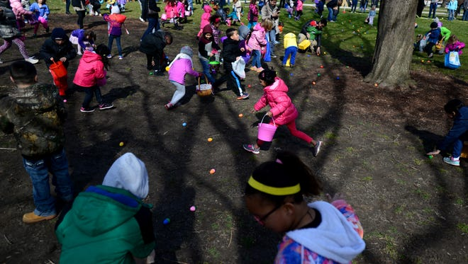 Children run out and grab Easter eggs in front of the Capitol on Saturday during the Lansing Jaycees' Easter Egg Hunt.