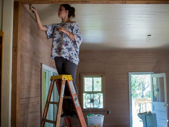 Amber Reggiatore paints the interior of a home in Arnaudville,