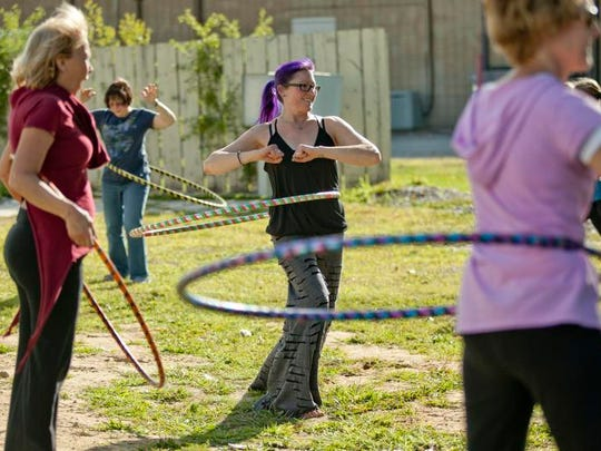 Instructor Jules Becker stands in the middle of a group during a hooping class.