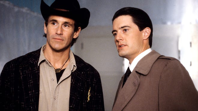 """FBI Special Agent Dale Cooper (Kyle MacLaughlin, right) tells local Sheriff Harry S.Truman (Michael Ontkean) about his dream of former homecoming queen Laura Palmer's murder and his belief that the dream is a code to ichael Ontkean, Kyle MacLaughlin solving the crime in the first season of """"Twin Peaks."""""""