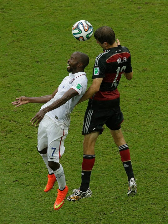 United States' DaMarcus Beasley, left, and Germany's Thomas Mueller battle for control of the ball during the group G World Cup soccer match between the USA and Germany at the Arena Pernambuco in Recife, Brazil, Thursday, June 26, 2014. (AP Photo/Hassan Ammar)