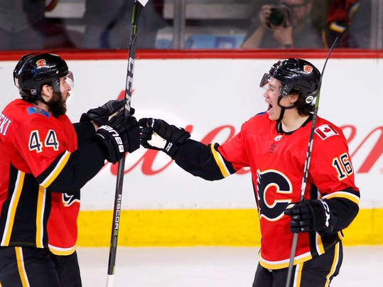 Calgary Flames' Spencer Foo, right, celebrates his goal against the Vegas Golden Knights with teammate Matt Bartkowski during the second period of an NHL hockey game Saturday, April 7, 2018, in Calgary, Alberta. (Larry MacDougal/The Canadian Press via AP)