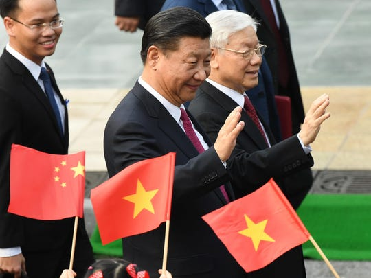 Chinese President Xi Jinping, center, and Vietnam Communist Party General Secretary Nguyen Phu Trong, right, wave during a welcoming ceremony at the presidential palace in Hanoi, Vietnam, Nov. 12.