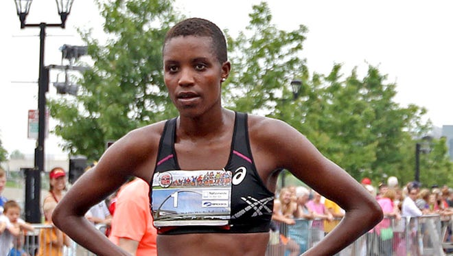 Diane Nukuri Johnson, of Iowa City, caught her breath after crossing the finish line to take first place in the Dam To Dam half marathon women's race in downtown Des Moines on Saturday morning May 31, 2014.