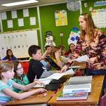 Gillett Elementary teacher Nicole Soper hands out an informational sheet to students in her 5th Grade class last week.