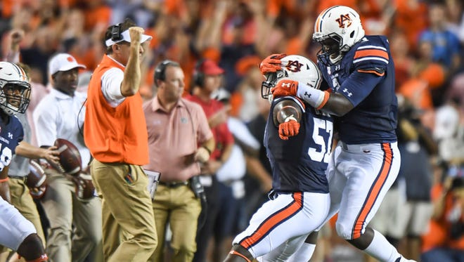 Auburn linebacker Deshaun Davis celebrating a play in front of Auburn head coach Gus Malzahn.