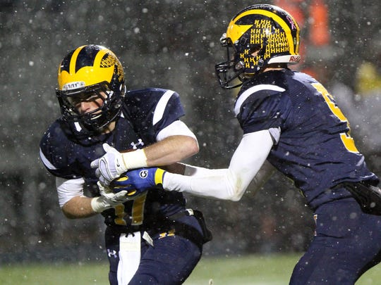 Hartland's Max Cadman takes the handoff from quarterback Noah Marshall in Friday's 14-0 loss to Grand Ledge in a Division 1 state playoff game.
