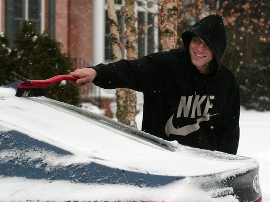 Alex Farinich of Morristown cleans off his car after Monday's snowstorm.