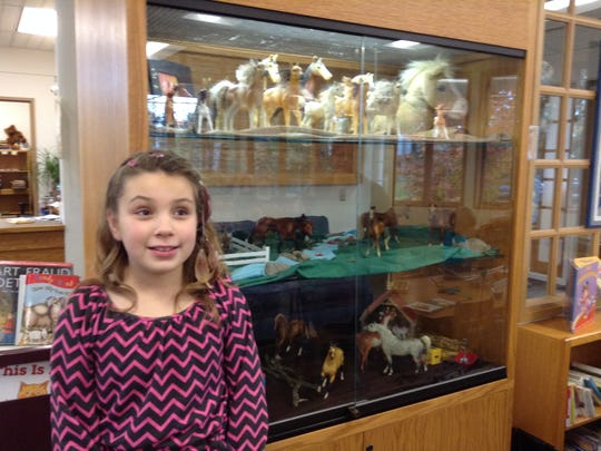 Aunika Thiessen beside her equine display at the Stayton Public Library.