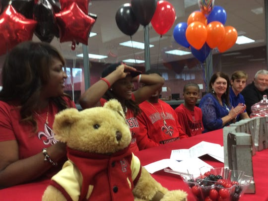 Pineville forward Danyale Bayonne dons a UL Lafayette cap after signing with the school Friday.