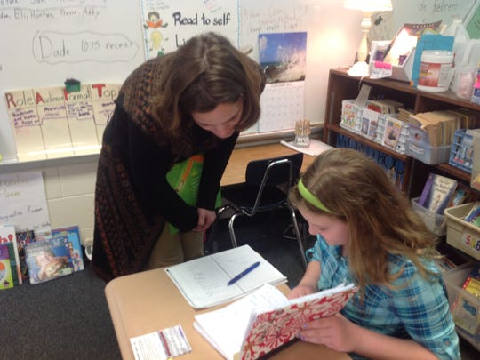 University of Wisconsin Marathon County Assistant Professor of English Jill Stukenberg works with a third grader on poetry at Mosinee Elementary School in February 2016.