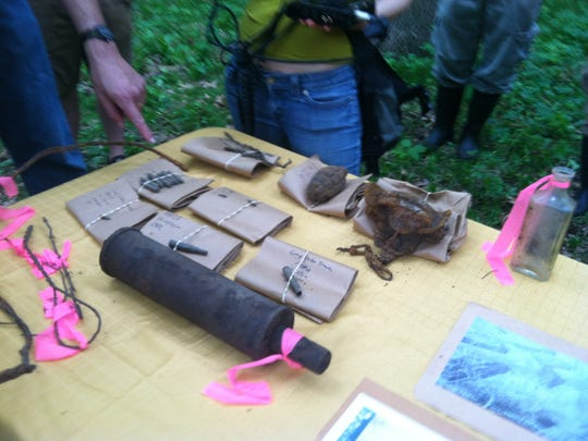 World War II military items dug up by an archaeology team at Camp Dodge were displayed near the remnants of training trenches in 2014.