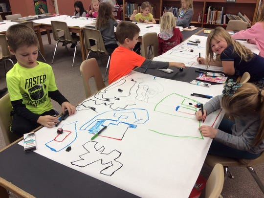 First- and second-graders create complex commands for their Ozobots using colored lines.