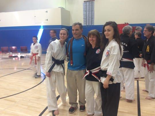 New black-belt karate artist Amy Allen, left, with her father, Richard; her mother, fourth-degree black belt Loretta, and her older sister, first-degree black belt Rachel.