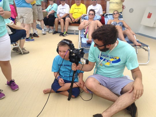 Max Morgan helps a student from Ringling College of Art and Design make a documentary during the 2015 Buddy Cruise. Max will return for his fourth cruise for families affected by Down syndrome and other disabilities this October.