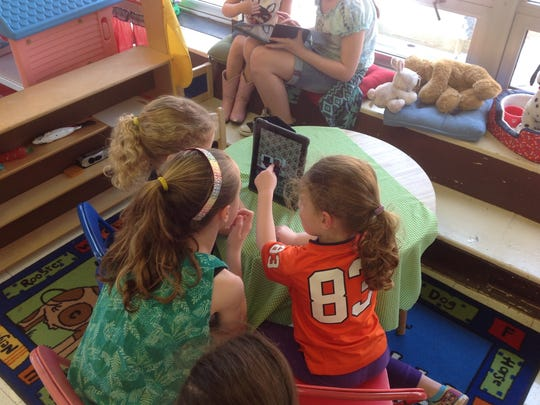 Stoy students gather around one of their iPads during class.