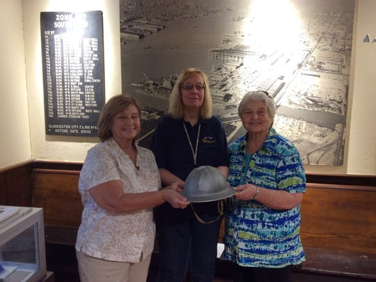 Daughters of a New York Shipbuilding Corp. worker Bob Kutz present their dad's 1936 hard hat to Leslie Watson (center), collection manager, at the opening of the new Camden Shipyard and Maritime Museum on Sunday. Daughters are Roberta Seran of South Carolina (left) and Kay Simione of Franklin.