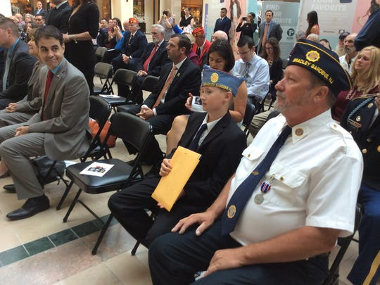 Veterans and members of their families watch as veterans