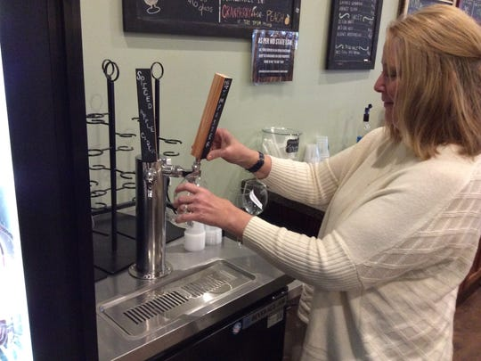 Tasting room worker Pam Payne pours a glass of Imposter. The wine is put into kegs and served through a tap, just like traditional draft beers.