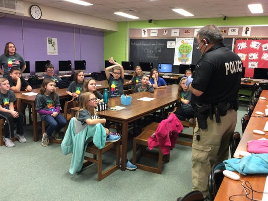 Police officer Jeff Hart leads a discussion with SES students about the importance of fingerprint identification.
