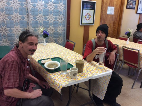 Mark Lesko, left, and John Cooper finish up a late lunch at the Global Grace Cafe, a restaurant where the food is prepared by refugees at the Reformed Church of Highland Park.