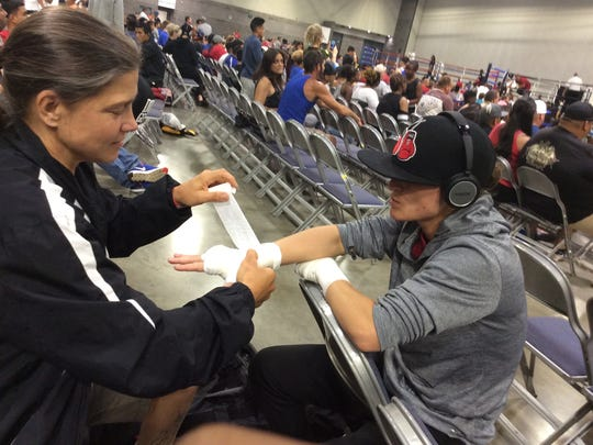 Coach Andrea Nelson wraps boxer Sadie Roberts' hands before a bout in Hot Springs, Arkansas, at TITLE Boxing Nationals in early June 2017.