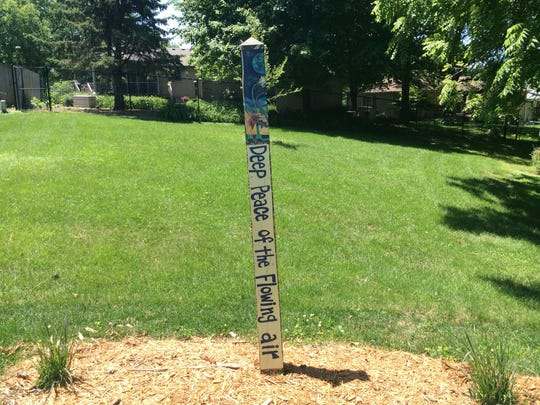 Garden art poles are all the rage this year. These are wooden square poles with a triangle at the top, painted in colorful designs and usually with words or sayings on them. This one is in the labyrinth at First Presbyterian Church