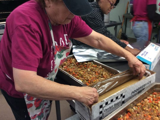 Volunteer Marilyn Kayak, left, and chef Pam Johnson, right, prepare trays of stew for the oven at Elijah's Promise in New Brunswick.