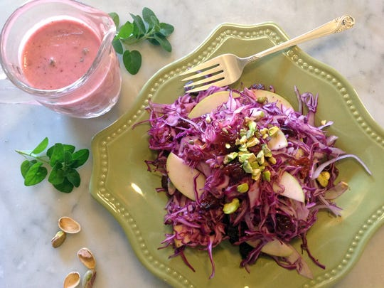 Red cabbage is tossed with apple, pistachios, red onion