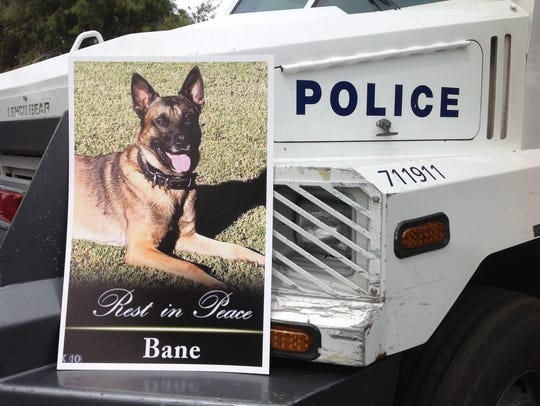 A police vehicle with a picture of Bane, the fallen K-9 officer at his memorial service.