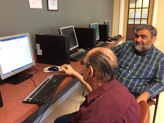 Veteran and Valley Brook resident Mike Broznak works on a computer while employment counselor Julio Richards coaches him.
