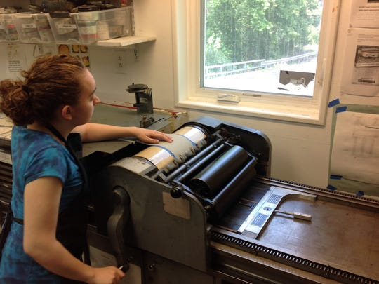 Intern Grace Ann Castellano printing letterpress on handmade paper from military uniforms.