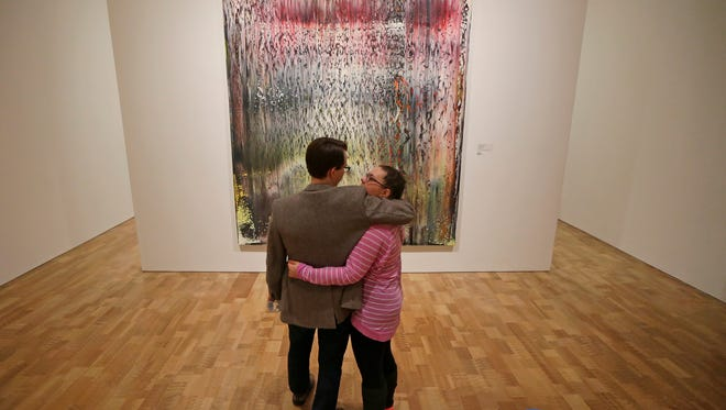 """Matt Albertini and Alyssa Bell, both of Milwaukee, check out a painting in the gallery titled """"Breath"""" by Gerhard Richter at MAM After Dark."""