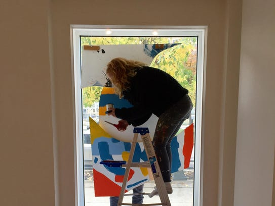Detroit artist Ellen Rutt works on a window installation