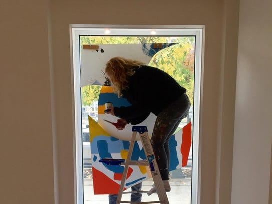 Detroit artist Ellen Rutt works on a window installation