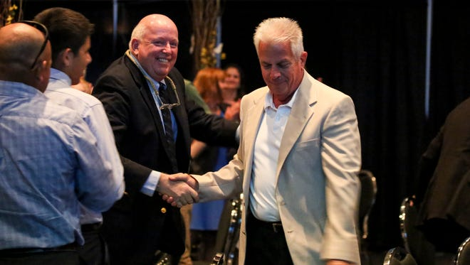 Ellis Etter shakes hands with Paul McCarthy, President and Owner of Captiva Cruises, Inc., as he walks to the stage after being announced as the 2016 Junonia award winner. Lee County held it's 2016 Chrysalis Awards, a Celebration of Business & Tourism program, luncheon and trade show at Harborside Event Center, Fort Myers, to honor people who make a difference that help our economy and the community overall.