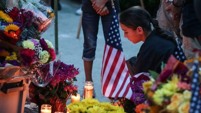 """A Palm Springs resident kneels near the memorial for fallen officers Jose """"Gil"""" Vega and Lesley Zerebny on Sunday during a vigil outside police headquarters."""