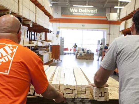 two men pushing cart of wood down an aisle in Home Depot store