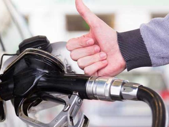 Man filling car with gas and giving thumbs up