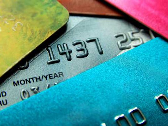 Multicolored credit cards in a messy pile.
