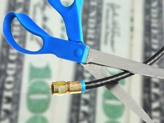 A cable cord is cut with scissors, with hundred dollar bills in the background.