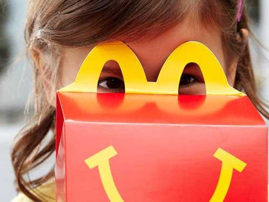 A child looks through the top of a happy meal box.