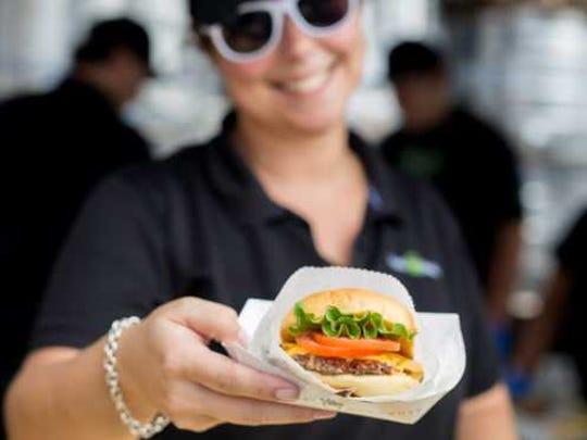 Shake Shack employee holding a burger.