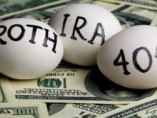 Eggs with IRA, 401K, Roth written on them laying on a pile of cash..