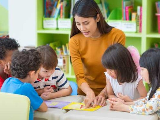 A child care provider working with a group of children.