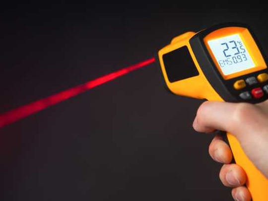 Hand holding and pointing an infrared thermometer.