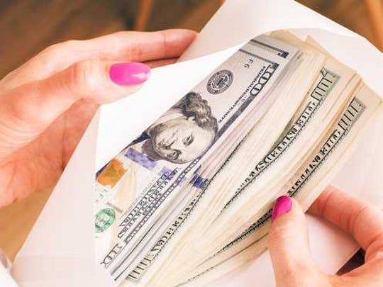 Woman holding an envelope full of cash.