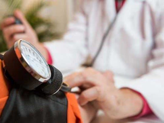 patient having blood pressure measured by doctor